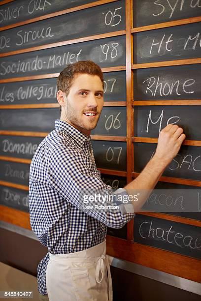 Man writing menu on blackboard