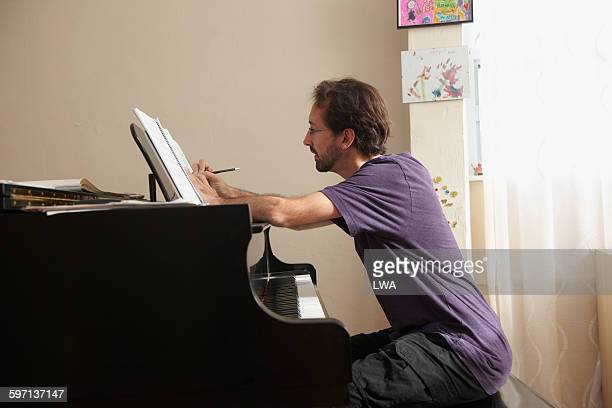 man writing music at piano - komponist stock-fotos und bilder