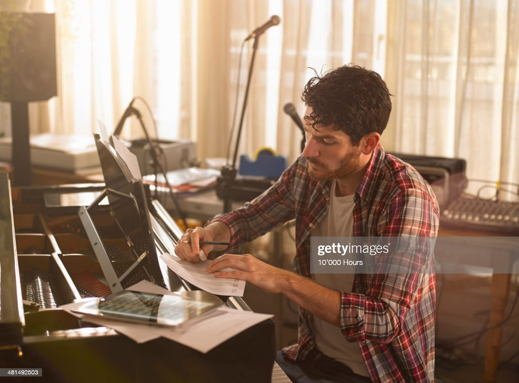 Man writing music on piano and a tablet computer : Stock Photo