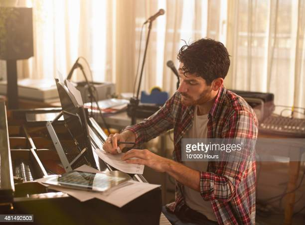man writing music on piano and a tablet computer - komponist stock-fotos und bilder