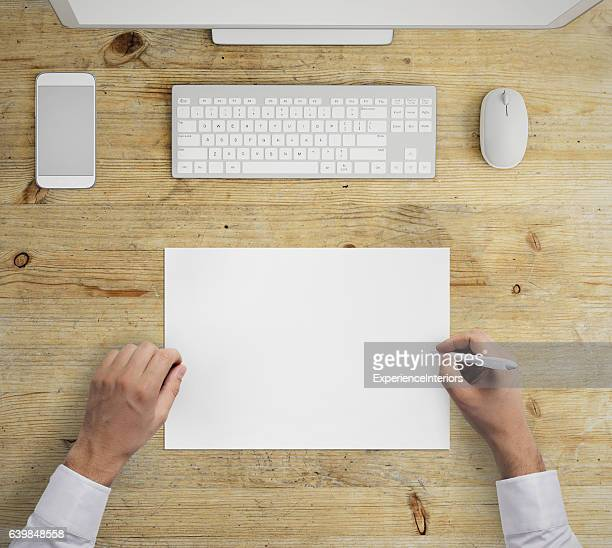 Man writing on a blank paper knolling