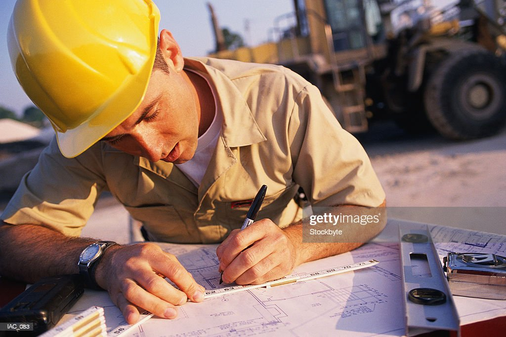Man Writing On Blueprint Wheel Loader In Background Stock