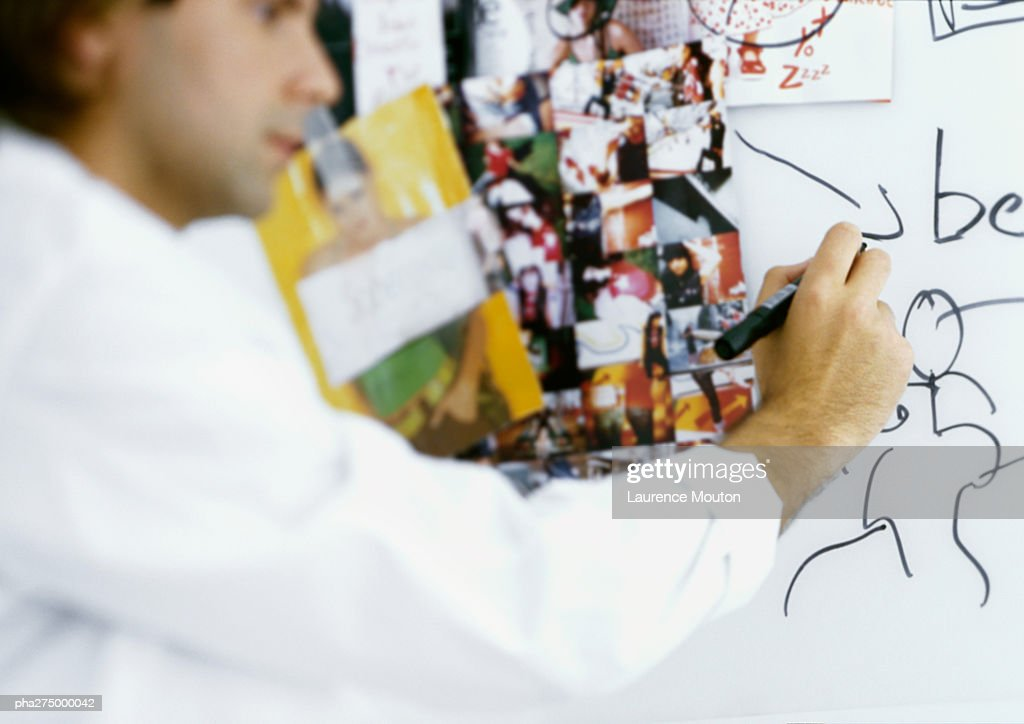 Man writing on board with images taped to it : Stockfoto