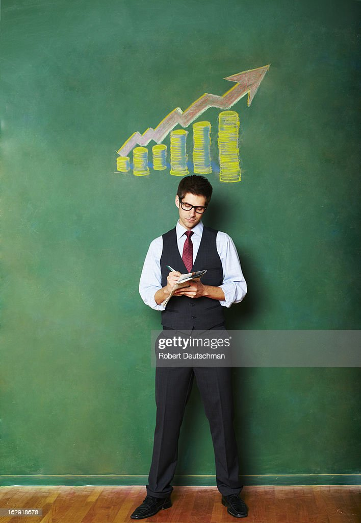 A man writing on his newspaper. : Stock Photo
