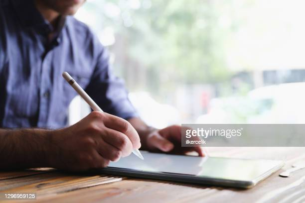 man writing or signing on digital tablet using stylus - agreement stock pictures, royalty-free photos & images