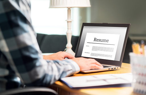 Man writing resume and CV in home office with laptop. Applicant searching for new work and typing curriculum vitae for application. Job seeking, hunt and unemployment. 1012049012