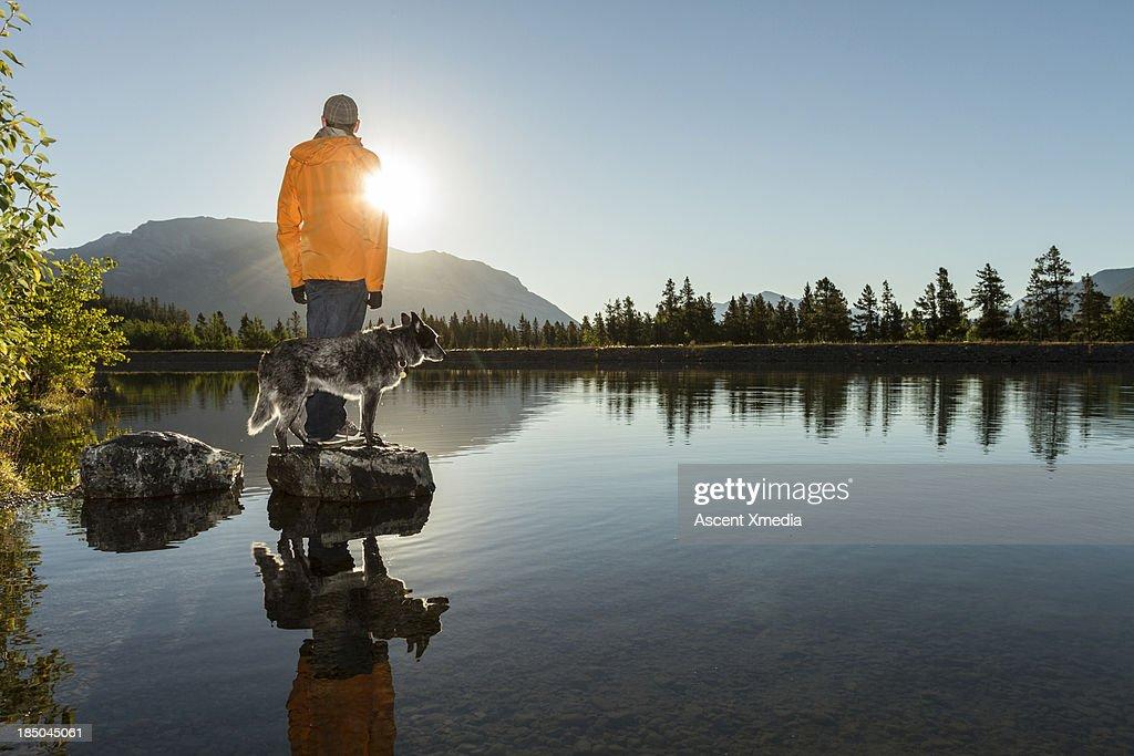 Man wtahces sunrise over mountains, with dog : Stock Photo