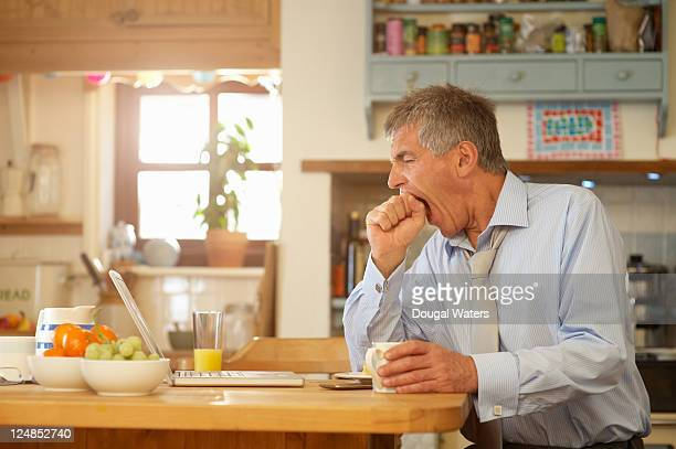 man yawning at kitchen table with laptop. - yawning stock pictures, royalty-free photos & images