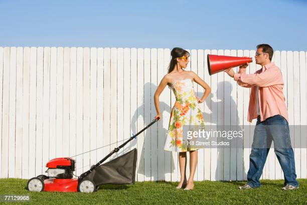 Man yelling at wife pushing lawn mower
