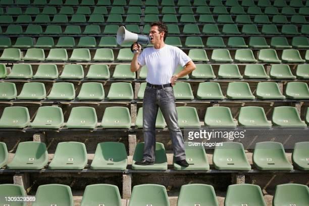 man yelling into bullhorn on green stadium seats - トピックス ストックフォトと画像