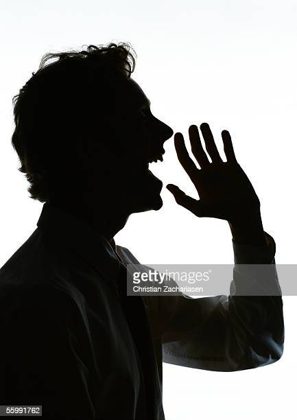 Man yelling with hand out in front of mouth, silhouette.