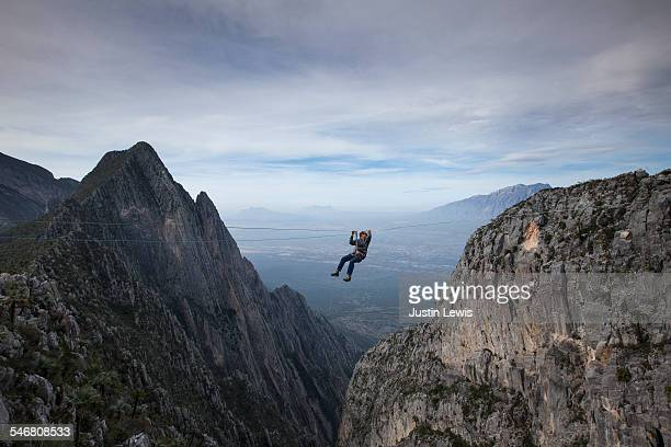 man zip lines across canyon - nuevo leon stock pictures, royalty-free photos & images