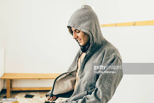 Man zipping up hooded top looking down smiling