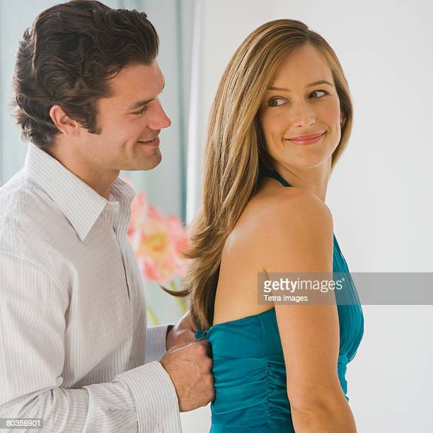 Man zipping up wife's dress