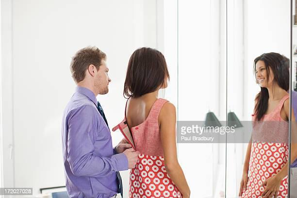 Hombre ' zipping mujer de vestido de ella