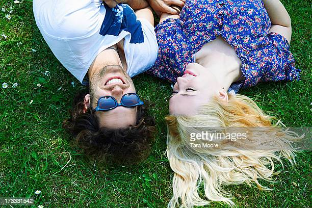 mana and woman smiling and lying on grass