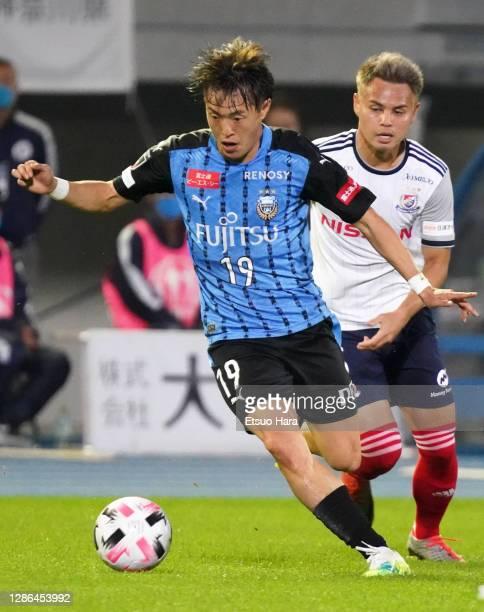 Manabu Saito of Kawasaki Frontale and Theerathon of Yokohama F.Marinos compete for the ball during the J.League Meiji Yasuda J1 match between...