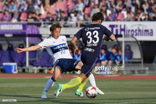 Manabu Saito of Yokohama FMarinos and Tsukasa Shiotani of Sanfrecce Hiroshima compete for the ball during the JLeague J1 match between Sanfrecce...