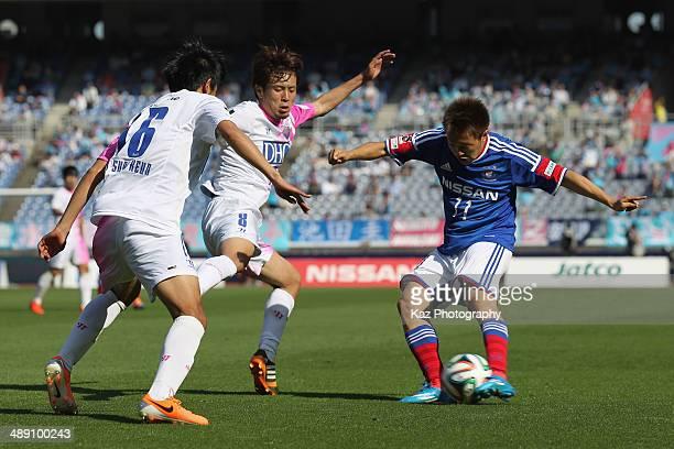 Manabu Saito of Yokohama F.Marinos competes for the ball against Kota Mizunuma and Choi Sung-Keun of Sagan Tosu during the J.League match between...