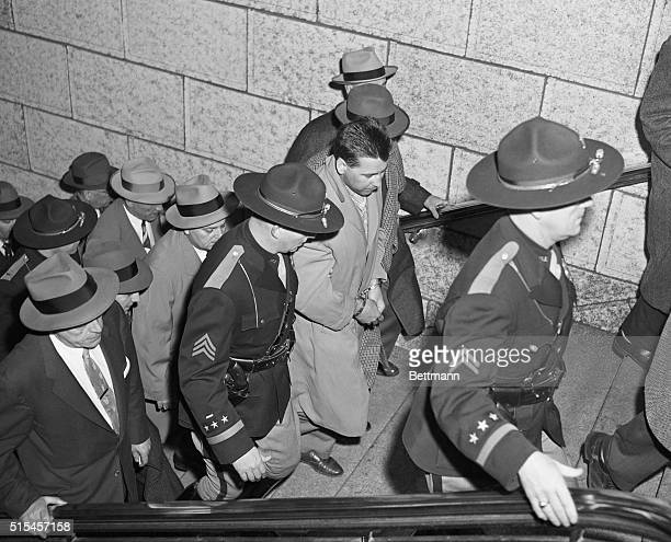 A manacled Leslie Mad Dog Irvin and surrounded by heavy guard of Chicago and Indiana police is led from Union Station here for transfer to the...