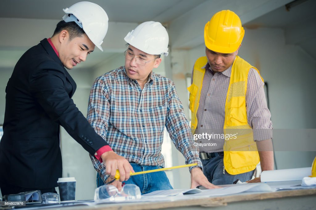 Management consulting and engineers and foreman working with management consulting and engineers and foreman working with blueprint and drawing on work table malvernweather Choice Image