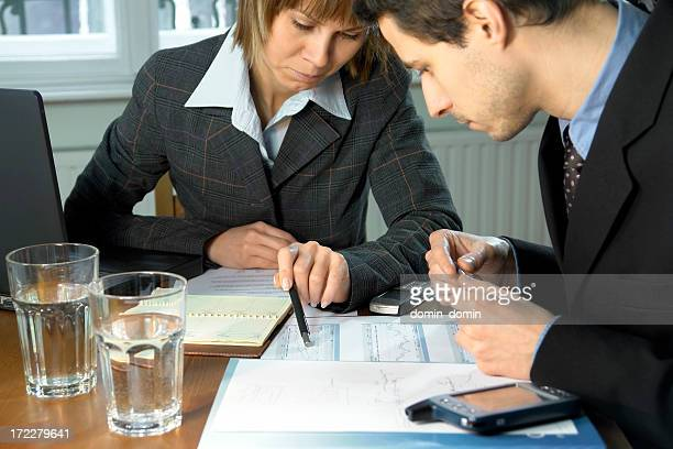 Management team discusses schema, chart lying on desk, home interior