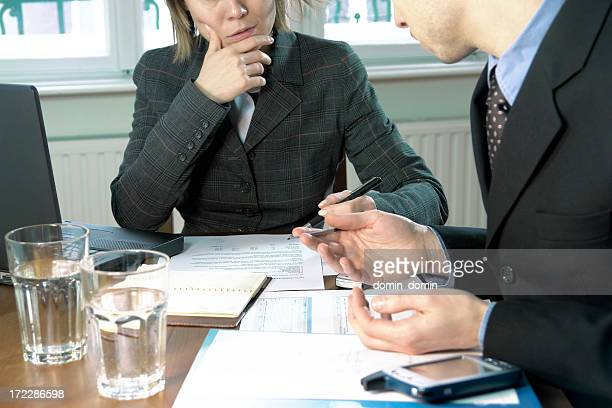 Management team discussing schema, chart lying on desk, home interior