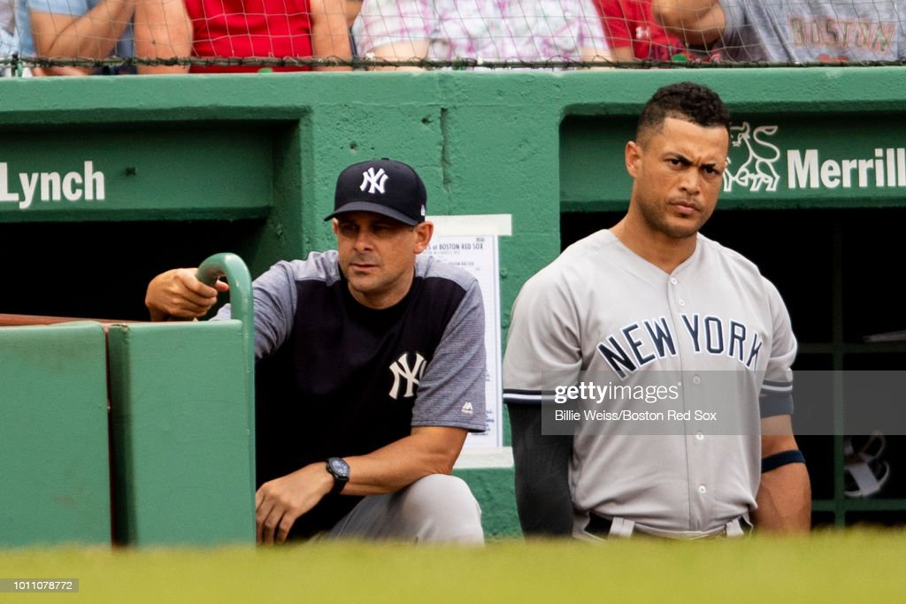 Manager Aaron Boone and Giancarlo Stanton #27 of the New York Yankees look on during the ninth inning of a game against the Boston Red Sox on August 4, 2018 at Fenway Park in Boston, Massachusetts.