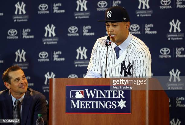 Manager Aaron Boone looks on as Giancarlo Stanton speaks during a press conference where he is introduced as a member of the New York Yankees at the...
