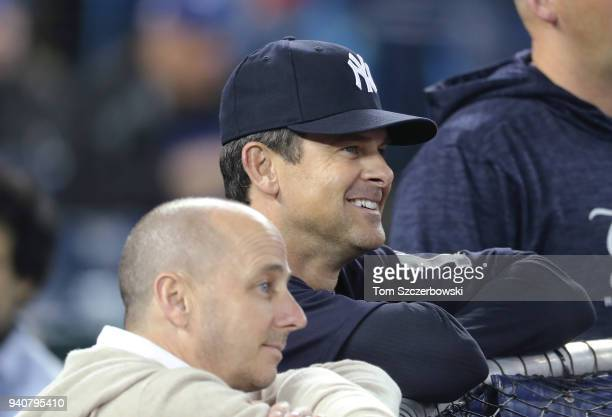 Manager Aaron Boone of the New York Yankees and general manager Brian Cashman look on during batting practice before the start of MLB game action...