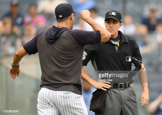 Manager Aaron Boone of the New York Yankees argues with home plate umpire Brennan Miller during the second inning of game one of a doubleheader...