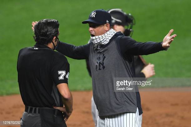 Manager Aaron Boone of the New York Yankees exchanges words with umpire John Tumpane during the first inning against the Miami Marlins at Yankee...