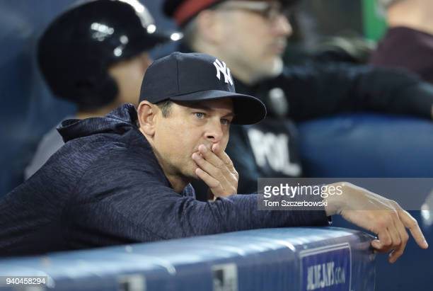 Manager Aaron Boone of the New York Yankees looks on from the dugout on Opening Day during MLB game action against the Toronto Blue Jays at Rogers...