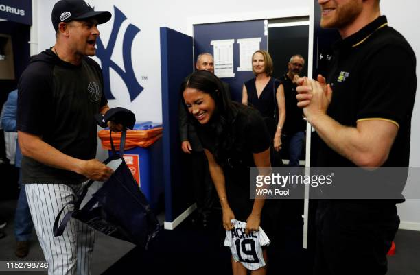 Manager Aaron Boone of the New York Yankees presents a gift for Archie to Prince Harry Duke of Sussex and Meghan Duchess of Sussex before their game...