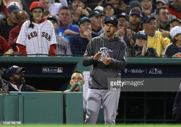 Manager Aaron Boone of the New York Yankees reacts after Didi Gregorius struck out looking as a Boston Red Sox fan looks on during the sixth inning...