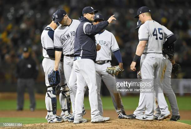 Manager Aaron Boone of the New York Yankees takes the ball from pitcher JA Happ to make a pitching change against the Oakland Athletics in the bottom...