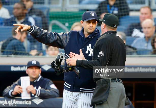 Manager Aaron Boone of the New York Yankees talks with home plate umpire Cory Blaser during the first inning against the Boston Red Sox at Yankee...