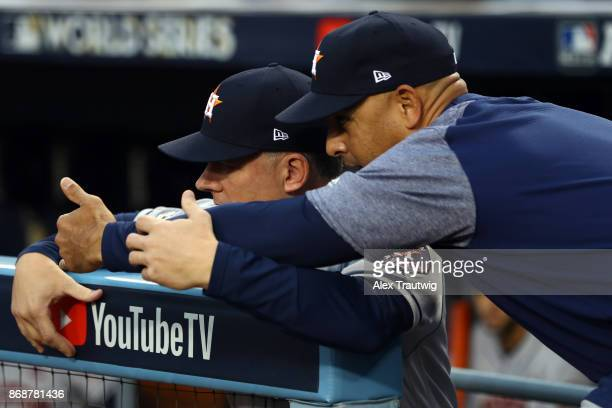 Manager A.J. Hinch and bench coach Alex Cora of the Houston Astros talk in the dugout during Game 6 of the 2017 World Series against the Los Angeles...