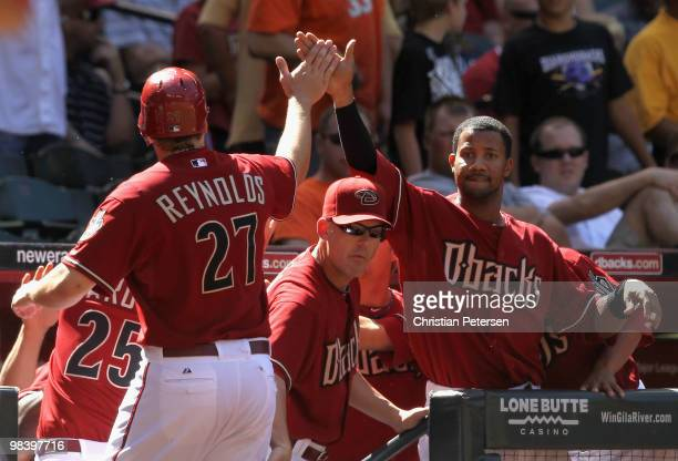 Manager AJ Hinch and Chris Young of the Arizona Diamondbacks congratulate teammate Mark Reynolds after scoring against the Pittsburgh Pirates during...