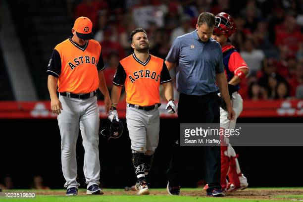 Manager AJ Hinch and Head athletic trainer Jeremiah Randall walk Jose Altuve of the Houston Astros to first base after he as hit by a pitch during...
