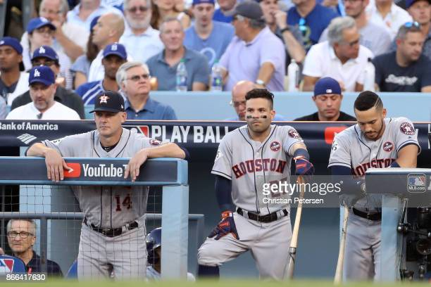 Manager AJ Hinch Jose Altuve and Carlos Correa of the Houston Astros look on from the dugout during the first inning against the Los Angeles Dodgers...