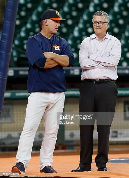 Manager AJ Hinch of the Houston Astros left and general manager Jeff Luhnow talk during batting practice before playing the St Louis Cardinals at...