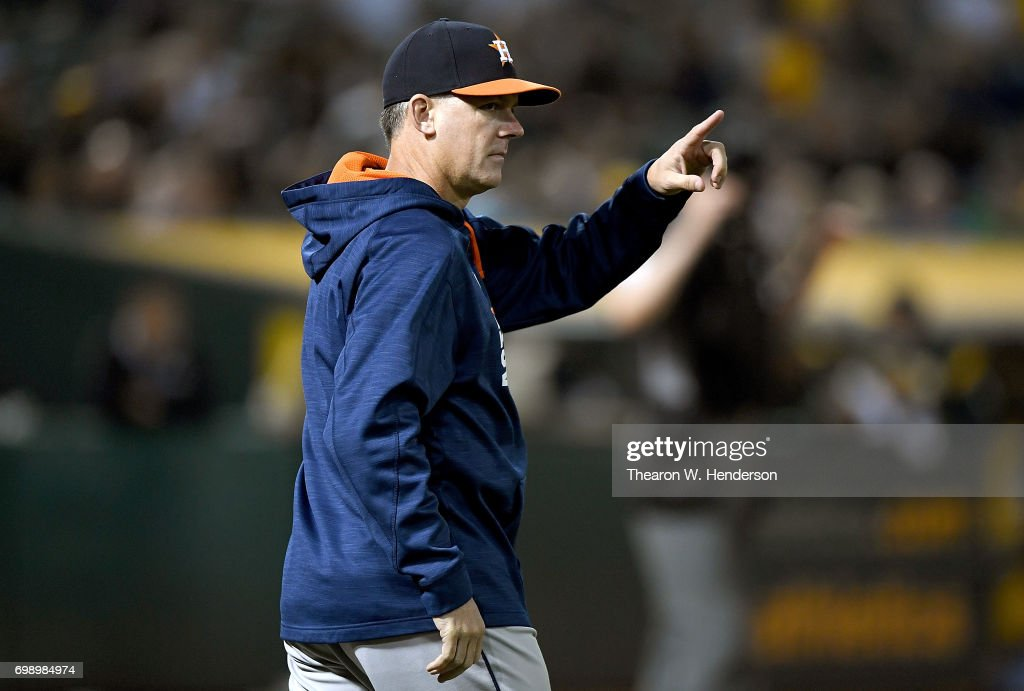 Manager A.J. Hinch #14 of the Houston Astros signals the bullpen to make a pitching change against the Oakland Athletics in the bottom of the six inning at Oakland Alameda Coliseum on June 20, 2017 in Oakland, California.