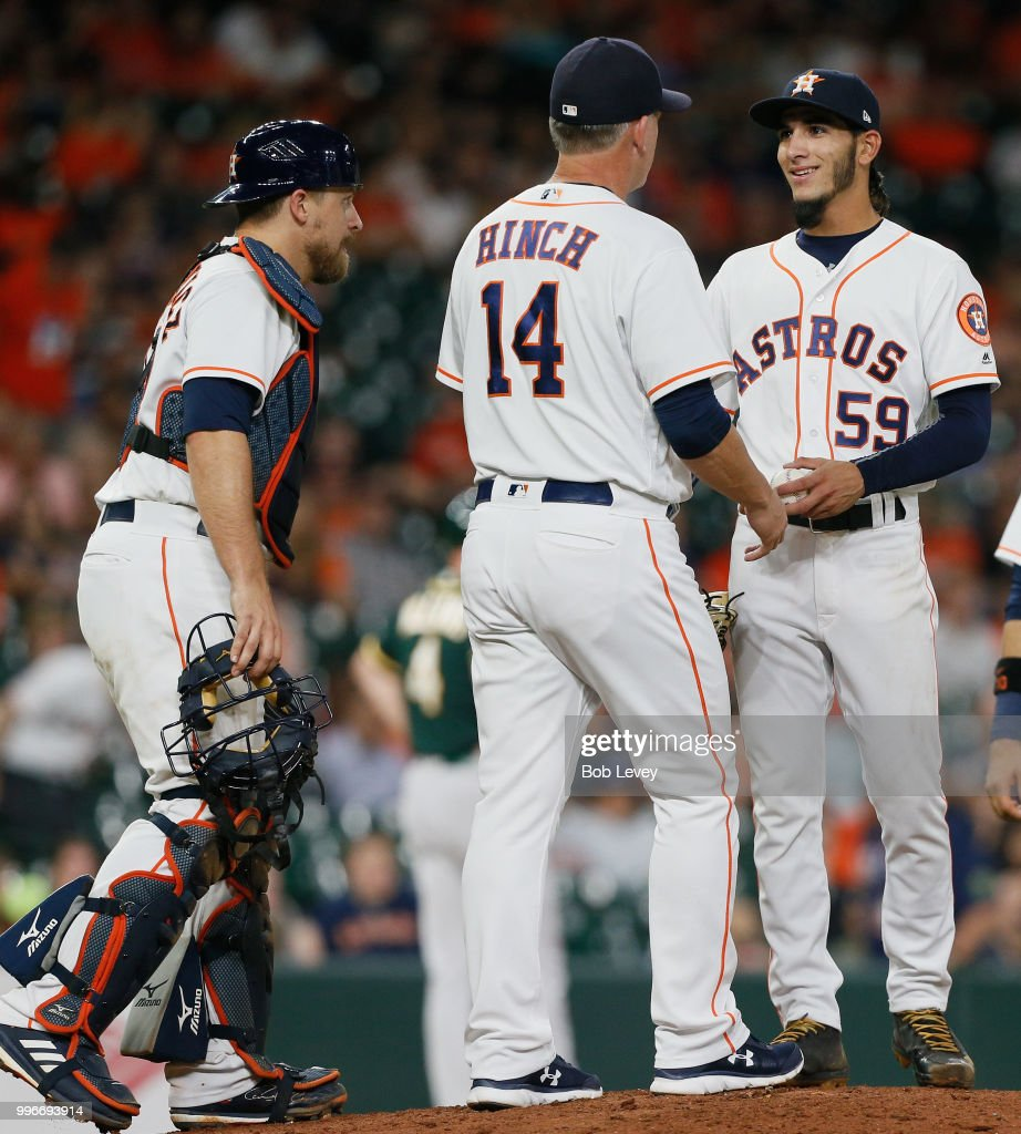 Manager AJ Hinch #14 of the Houston Astros takes the ball from Cionel Perez #59 in the ninth inning as Tim Federowicz #19 loks on at Minute Maid Park on July 11, 2018 in Houston, Texas.