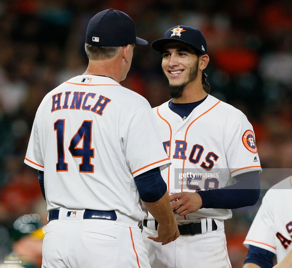 Manager AJ Hinch #14 of the Houston Astros takes the ball from Cionel Perez #59 in the ninth inning at Minute Maid Park on July 11, 2018 in Houston, Texas.