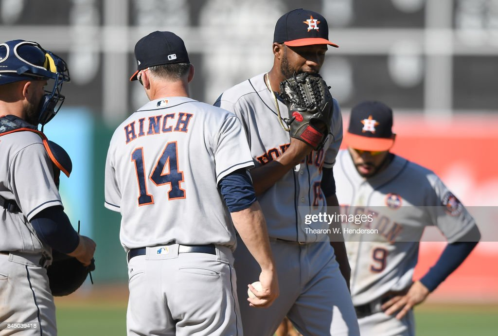 Manager A.J. Hinch #14 of the Houston Astros takes the ball from pitcher Reymin Guduan #64 taking him out of the game after Guduan walked five Oakland Athletics in a row in the bottom of the eighth inning during game one of a doubleheader at Oakland Alameda Coliseum on September 9, 2017 in Oakland, California.