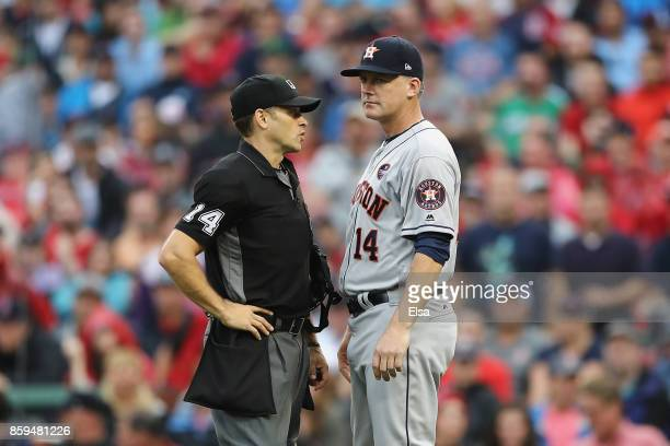 Manager AJ Hinch of the Houston Astros talks with umpire Mark Wegner during game four of the American League Division Series at Fenway Park on...