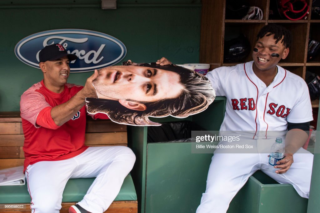 Manager Alex Cora and Rafael Devers #11 of the Boston Red Sox reacts with a big head cut out of Andrew Benintendi #16 before a game against the Texas Rangers on July 10, 2018 at Fenway Park in Boston, Massachusetts.