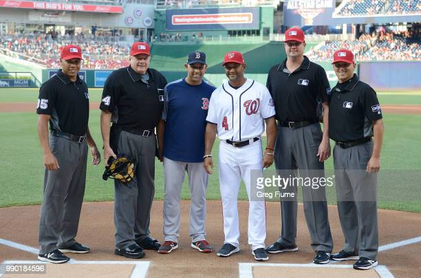 Manager Alex Cora of the Boston Red Sox and Manager Dave Martinez of the Washington Nationals pose for a photo with the umpire crew before the game...