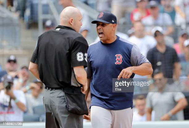 Manager Alex Cora of the Boston Red Sox argues with home plate umpire Mike Estabrook after Cora was tossed from the game in the fourth inning against...
